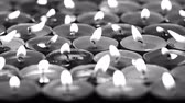 religious symbols : UHD monochrome slow dolly of candles burning in the dark