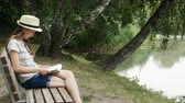 okumak : A young girl reading a book on a bench near the lake