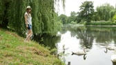 mere : Female in panama feeds swans on the pond in the summer park.