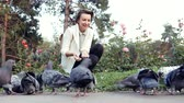 piccione : Young pretty girl feeds pigeons in park. Flock of birds eating a bread outdoors
