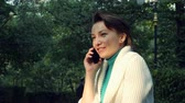 comunicare : Close up female with short hair talking and Smiling mobile phone in the park