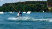 A Man Jumping His Wakeboard Off A Ramp At Cable Park, Slow Motion. Water Skiing