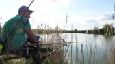 フィッシャー : Fisherman sits on the bushy grass shore lake and fishing. Sunny day. Side view.