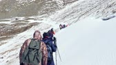 Group of people going to the snowy mountain. Climber Alpinist. Shoot from behind