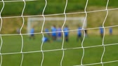 Children soccer game from behind goal net Stok Video