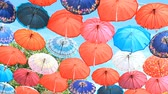 napernyő : Multicolored umbrellas hanging on blue sky background Stock mozgókép