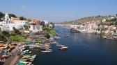 Шива : Omkareshwar, India - circa November, 2017: Omkareshwar cityscape, India, sacred hindu temple. Holy Narmada River, floating boats. Travel destination for tourists and pilgrims. Стоковые видеозаписи