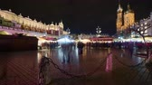Timelapse of the crowded Rynek Christmas market in the center of Krakow, Poland, in the background to the left Sukiennice the cloth market and to the right the St Mary Basilica.