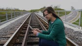 emelvény : Young smiling girl using tablet and standing at railway. Wearing glasses and dressed in green. Stock mozgókép