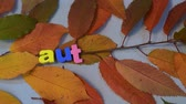tipo de letra : Male hand, write word autumn with colorful letters on yellow leaves background.