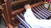 шпагат : skilled craftsman weaves a fabric with an ancient hand loom using the wire and the spool