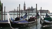 Венеция : Many gondolas to transport tourists moored in Venice near Saint Mark Square and the Church of Saint George