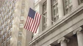 wealthy : Semi side shot of American flag waving in a calm breeze off a historical financial building on the Wall Street in Lower Manhattan, New York, United States Stock Footage