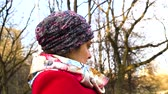 ninhada : The girl in the hat, neck scarf and a red coat sitting thoughtfully Stock Footage