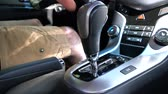 leva : A man switches the selector of the automatic transmission in Parking mode Filmati Stock