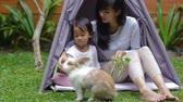 namiot : family sitting in tent and feeding the rabbit at home backyard