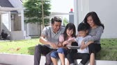parente : family in front of their house using tablet