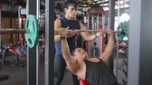 truhe : Man doing weigths on a bench press with the help