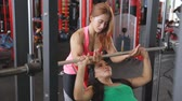 Woman doing weigths on a bench press with the help