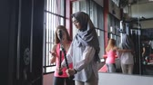 resistência : Young woman hijab doing arms exercises with trainer