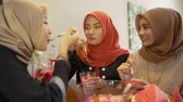 Veiled young women enjoy together a fruits cocktail