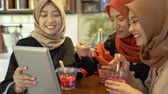 ramazan : Veiled young women relaxing with chatting and joking using digital tablet Stok Video