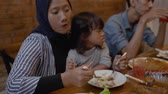 muslim mom eat with her daughter sitting on lap