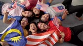 gloria : excited asian young supporter holding malaysia flag