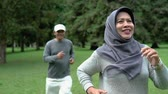 life is good : senior man and woman jogging together in the park Stock Footage
