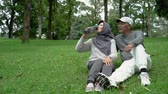 femme musulmane : senior couple with a bottle of water sitting in the garden Vidéos Libres De Droits