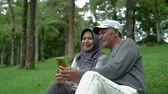 life is good : senior muslim couple using smartphone together in the park