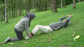 life is good : old man doing sit up in the park with wife