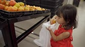 koupit : cute little girl take some tomato put it on the plastic bag when shooping Dostupné videozáznamy