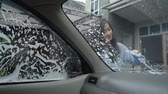 úmido : woman wash her car window with soap