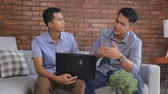 de brainstorming : two young casual male discuss using laptop Stock Footage