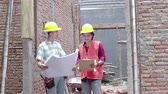 samen bouwen : two construction worker standing in the building site Stockvideo
