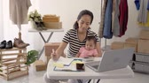 comerciante : woman with baby working from home of her online ecommerce shop Vídeos