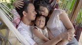 Asian family while resting on hammock