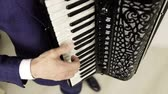 accordionist : The accordionists fingers run over the black and white keys.