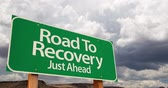 aviso : 4K Time-lapse Road To Recovery Green Road Sign and Stormy Cumulus Clouds and Rain.
