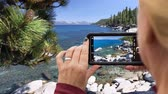 akıllı : 4k Looping Cinemagraph of Woman Filming Lake Shore Landscape on Smart Phone.