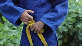 cinto : Tying the judo belt. Man ties kimono belt