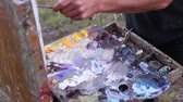 yağlı : Plein Air Painting. Hands of the artist. A painter arranges and mixes paints. En plein air painters painting Stok Video