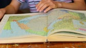 topografia : World Atlas. A person leafs through the political atlas of the modern world. Turning from page to page