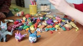 plasticina : Children playing with colored plasticine figurines of animals. Focus foreground