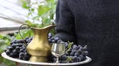 džbán : Man with silver tray. Red Wine Grapes. Copper jug ??and wineglass