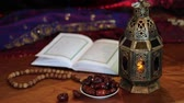 brunei : Quran, dates, arabian lantern and rosary. Breaking fast. Ramadan month at night with lights in the background