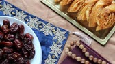 eid celebration : Islamic Celebration Foods and Quran. Celebrating Eid al-Fitr, the End of Ramadan, With Sweet, Traditional Treats Stock Footage