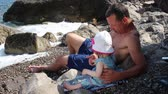 Çocuk bakımı : Father with a girl on vacation. Man With Little Girl Has Fun Sits On Pebble Beach Under Sea Surf Waves Stok Video