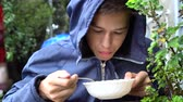 başlık : A teenager is eating outside in the rain